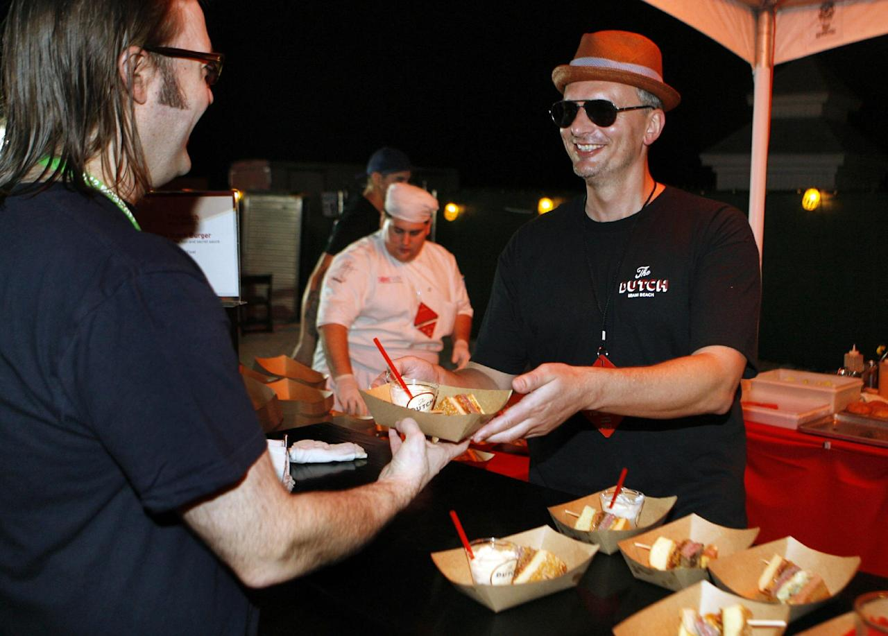 Chef Andrew Carmellini shares his Dutch Burger while competing in the Burger Bash at the Food Network South Beach Wine & Food Festival in Miami Beach, Fla., Friday Feb. 24, 2012. (AP photo/Jeffrey M. Boan)