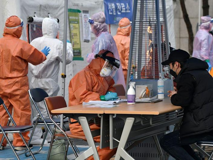 A medical staff member talks with a man at a testing facility in Seoul, South Korea, March 4, 2020.
