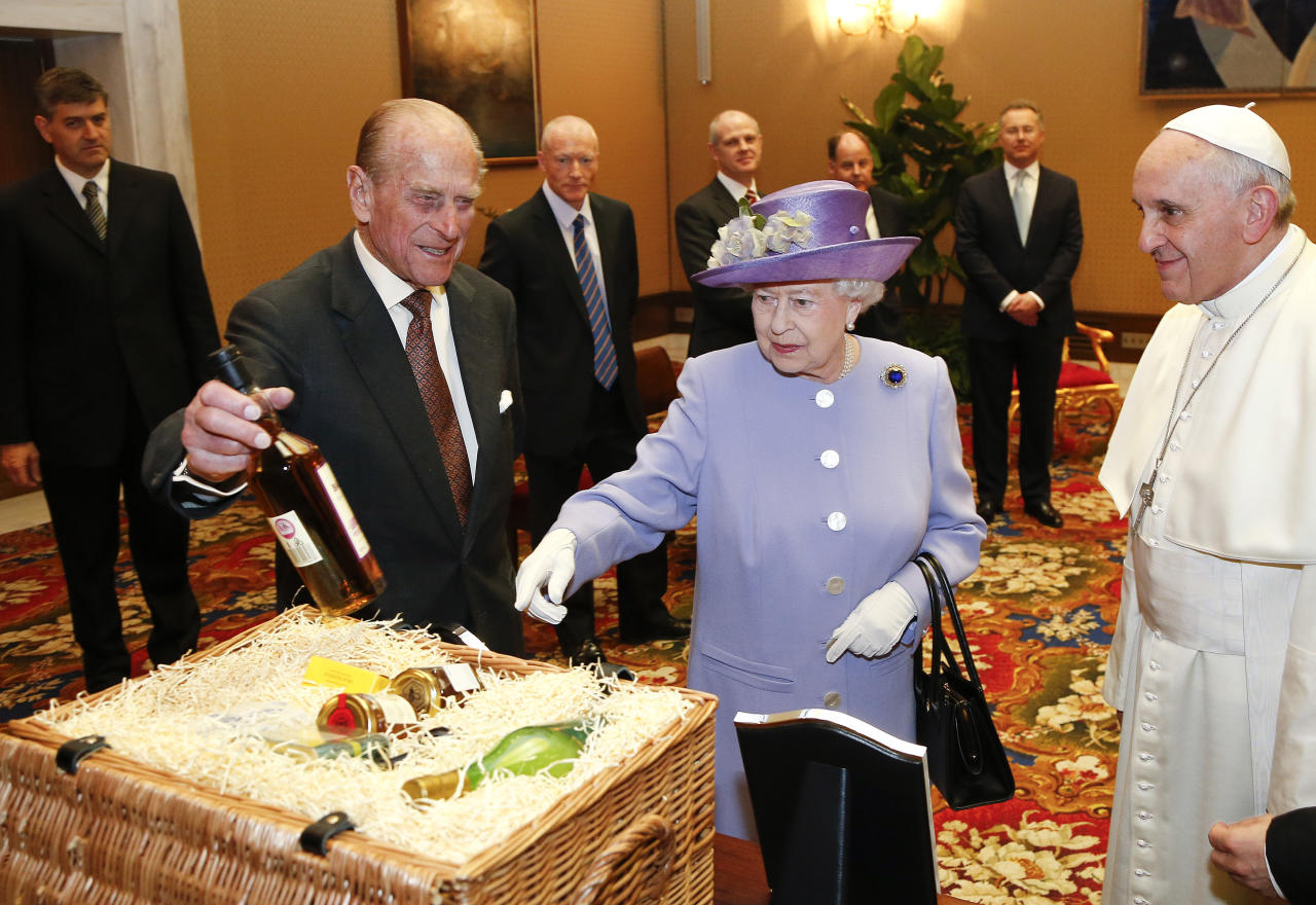 Britain's Queen Elizabeth II and Prince Philip, Duke of Edinburgh, exchange gifts with Pope Francis at the Vatican, Thursday, April 3, 2014. Queen Elizabeth II has come to Rome for lunch with Italy's president Giorgio Napolitano ahead of the British monarch's first meeting with Pope Francis. Before Francis, Elizabeth had met with four pontiffs, starting with Pope Pius XII in 1951, a year before her accession to the throne. (AP Photo/Stefano Rellandini, Pool)