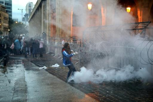 A Lebanese anti-government protester kicks back a tear gas canister fired by riot police from behind a barricaded road that leads to parliament in central Beirut on Sunday