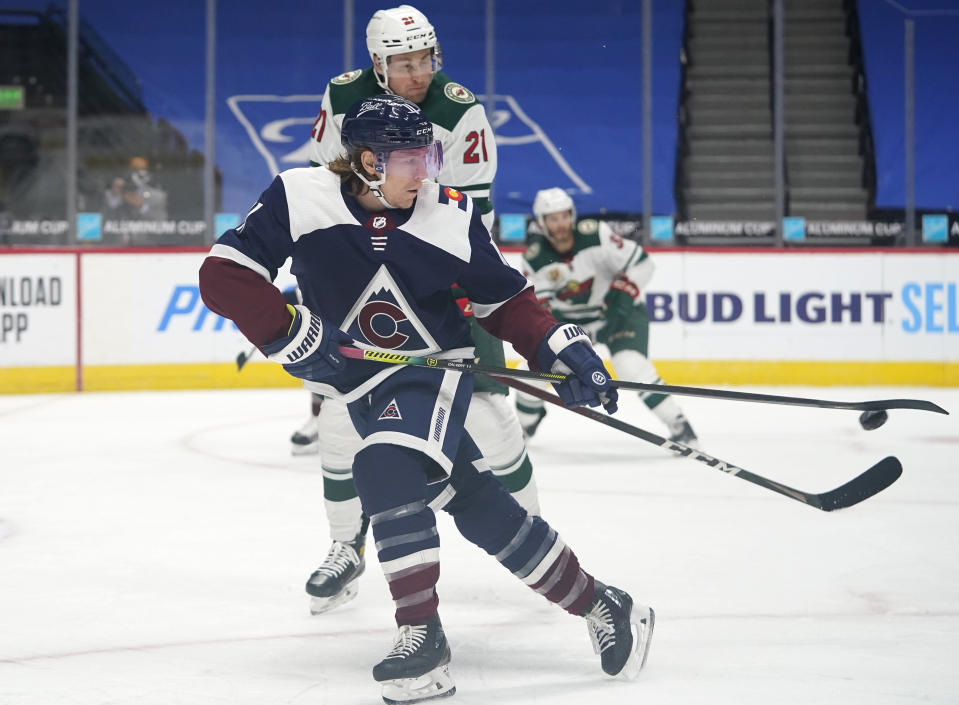 Colorado Avalanche left wing Matt Calvert, front, fields a pass as Minnesota Wild defenseman Carson Soucy covers in the first period of an NHL hockey game Wednesday, Feb. 24, 2021, in Denver. (AP Photo/David Zalubowski)