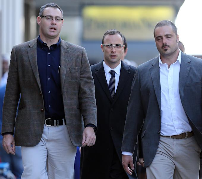 Oscar Pistorius, center, accompanied by his relatives, walks towards the high court in Pretoria, South Africa, Tuesday, April 8, 2014. Pistorius, who is charged with murder for the shooting death of his girlfriend, Reeva Steenkamp, on Valentines Day in 2013, was testifying for a second day at his murder trial Tuesday, answering questions from his defense lawyer. (AP Photo/Themba Hadebe)