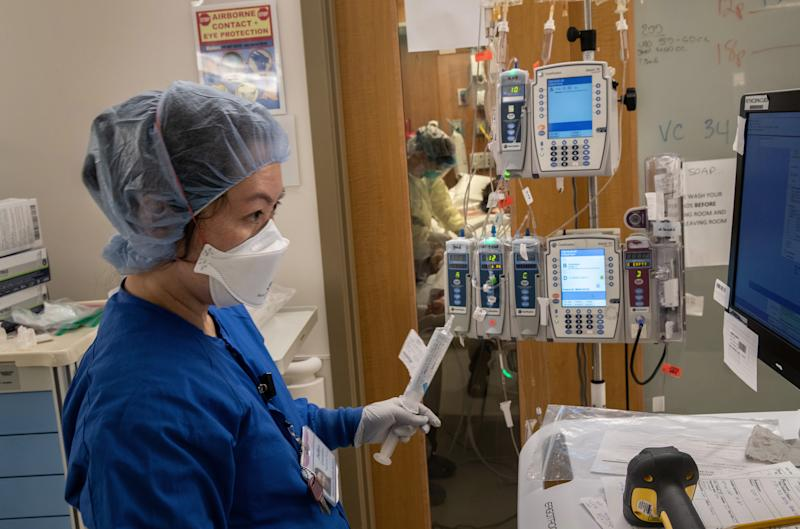 STAMFORD, CONNECTICUT - APRIL 24: (EDITORIAL USE ONLY) A nurse wearing an N95 mask works as intravenous therapy (IV) equipment hangs outside a COVID-19 patient's door in a Stamford Hospital intensive care unit (ICU), on April 24, 2020 in Stamford, Connecticut. Stamford Hospital, like many across the US, opened additional ICUs to deal the the vast number of people suffering in the coronavirus pandemic. Stamford, with it's close proximity to New York City, has the highest number of coronavirus (COVID-19) patients in Connecticut. (Photo by John Moore/Getty Images)