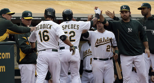 Oakland Athletics' Yoenis Cespedes (52) is congratulated after scoring against the Toronto Blue Jays in the first inning of a baseball game Monday, July 29, 2013, in Oakland, Calif. Cespedes scored on a sacrifice fly by Josh Reddick (16). (AP Photo/Ben Margot)