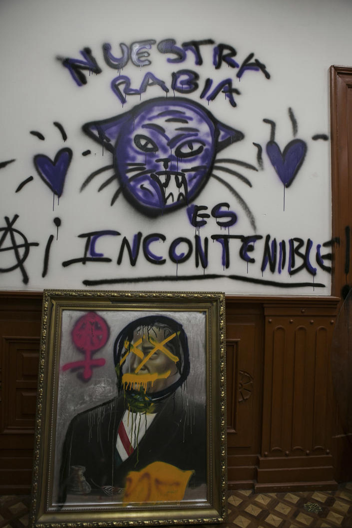 """A painting of former Mexican President Benito Juarez sits defaced under graffiti that reads in Spanish: """"Our anger is uncontainable,"""" done by women's rights activists inside the National Human Rights Commission (CNDH) office that they have been occupied for almost three months, using it as a refuge for victims of gender violence in Mexico City, Tuesday, Nov. 17, 2020. Feminist activists are occupying the building to demand justice for the victims of sexual abuse, femicide, and other gender violence, and are hosting some women and their children after the government either failed to solve or investigate sexual attacks on their daughters. (AP Photo/Ginnette Riquelme)"""