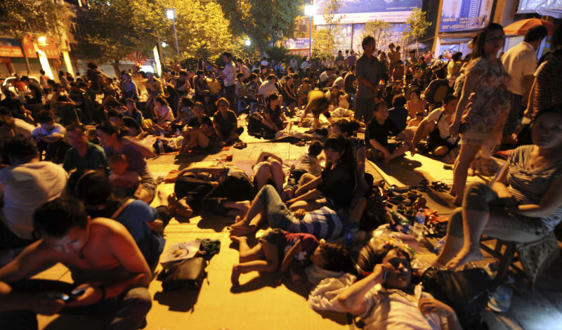In this photo released by China's Xinhua News Agency, residents rest on the ground at quake-hit Luozehe Town, Yiliang County, southwest China's Yunnan Province, early Saturday, Sept. 8, 2012. At least 80 people were killed and more than 100,000 residents were evacuated after Friday's quakes toppled thousands of houses and sent boulders cascading across roads in a remote mountainous area along the borders of Guizhou and Yunnan provinces. (AP Photo/Xinhua, Qin Qing) NO SALES