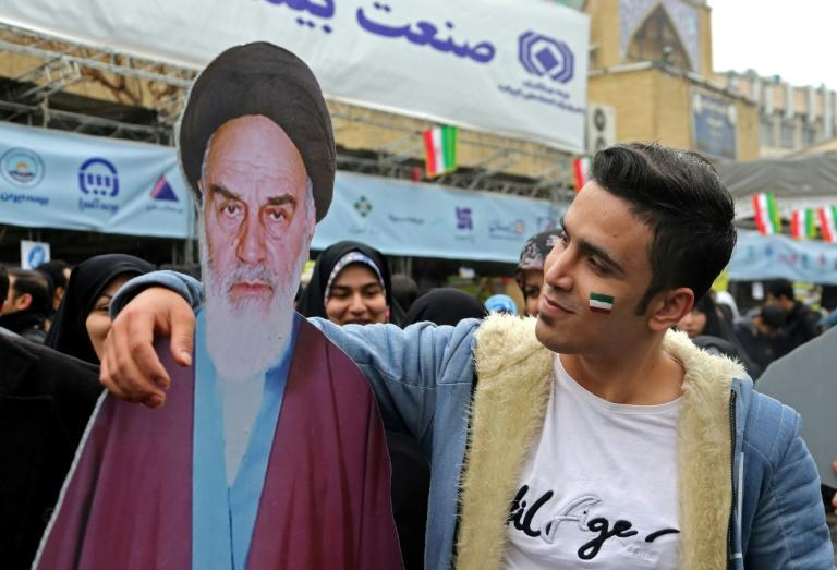 An Iranian man poses with a cutout of Ayatollah Ruhollah Khomeini during a ceremony celebrating the 40th anniversary of the revolution in the capital Tehran on February 11, 2019