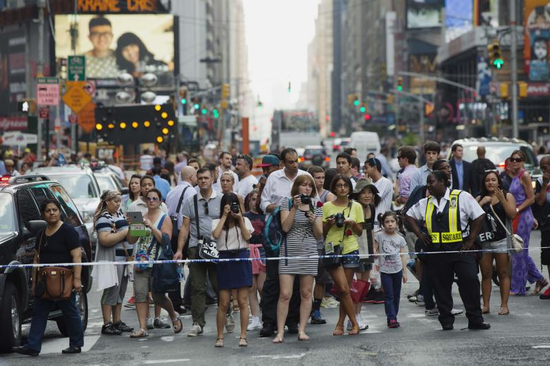 Pedestrians stop to look at the scene of a collision between two tour buses in the Times Square region of New York