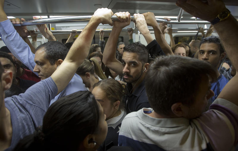 In this Aug. 7, 2013 photo, passengers ride a crowded subway train in Sao Paulo, Brazil. Chests squashed flat against backs, hours a day, every day. That's the daily commute for the 8 million citizens who ride the subway and bus lines each day in Sao Paulo, South America's largest city. (AP Photo/Andre Penner)
