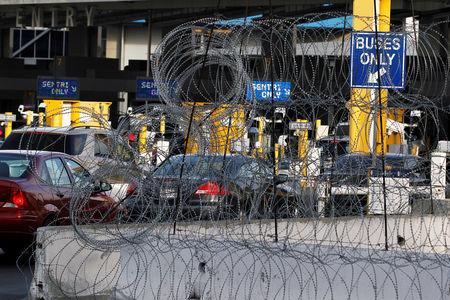 Cars are seen queue up in multiple lines through concertina wire as they wait to be inspected by U.S. border patrol officers to enter from Mexico into the U.S., at the San Ysidro point of entry, in Tijuana, Mexico April 1, 2019. REUTERS/Jorge Duenes