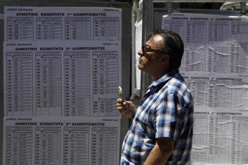 A pedestrian checks lists with polling stations one day before general elections in Athens, Saturday, June 16, 2012. Greeks vote for the second time in six weeks this Sunday amid fears that the country could be forced out of the euro if they reject the strict austerity measures taken in return for billions of euros in rescue loans from other European countries and the International Monetary Fund. (AP Photo/Kostas Tsironis)