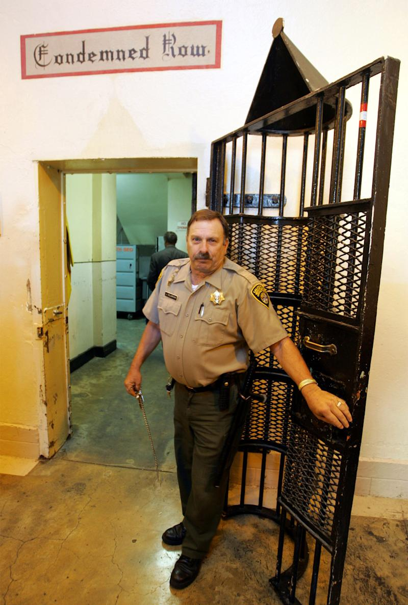 FILE - In this Oct. 25, 2004 file photo taken in San Quentin, Calif., Guard Joe Dellabruna opens an entrance to death row at San Quentin State Prison.  Seven years after Scott Peterson was sentenced to death for murdering his pregnant wife Laci, his appeal is moving at lightning speed, at least compared to those of his 725fellow California Death Row inmates. Appealing the death penalty in California can take two decades, meaning that condemned prisoners are more likely to die behind bars of natural causes than be executed. Now voters in California get an opportunity this November to vote on a measure that would abolish the death penalty. (AP Photo/Eric Risberg)