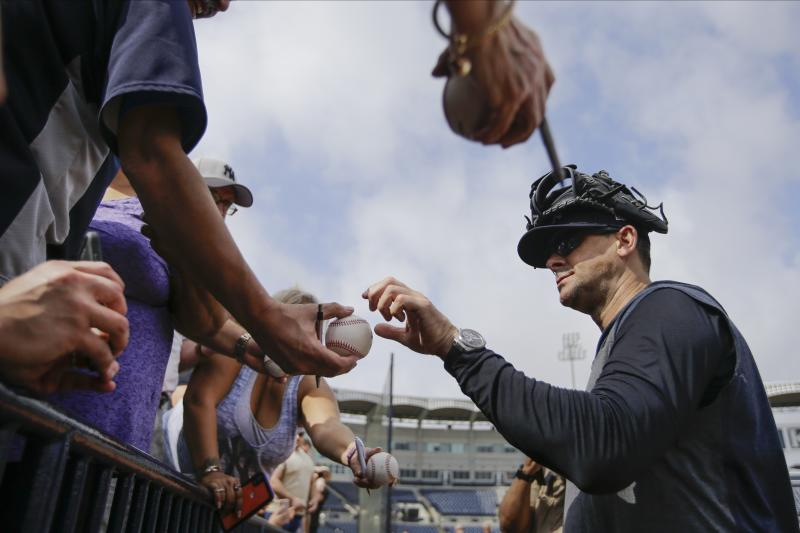 New York Yankees manager Aaron Boone signs autographs during a spring training baseball workout Thursday, Feb. 13, 2020, in Tampa, Fla. (AP Photo/Frank Franklin II)