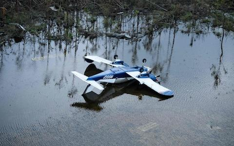 <span>A plane is turned upside down after Hurricane Dorian</span> <span>Credit: Brendan Smialowski/AFP </span>