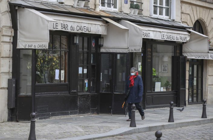 A woman wearing face a mask as a precaution against the coronavirus walks past a closed restaurant in Paris, Monday, Jan. 25, 2021. France's government may impose a third lockdown in the coming days if an existing 12-hour-a-day curfew doesn't significantly slow virus infections. (AP Photo/Michel Euler)