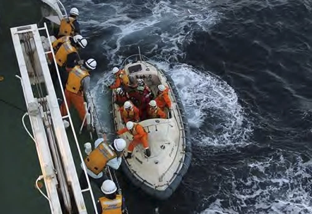 In this photo released by Japan Coast Guard, British adventurer Sarah Outen, at center in the small boat, prepares to board a coast guard patrol ship after she was rescued in the Pacific Ocean off northeastern coast of Japan, Friday, June 8, 2012. Outen's blog said she was hit by a storm during her attempted journey around the world, and that her boat rolled over and was damaged. Another Briton on a similar trek was still awaiting rescue. (AP Photo/Japan Coast Guard)