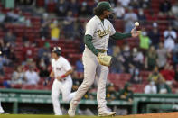 Oakland Athletics' Sean Manaea, right, gets a grip on the ball as Boston Red Sox's Hunter Renfroe, left, runs to home to score on a two-run home run by Bobby Dalbec in the second inning of a baseball game, Thursday, May 13, 2021, in Boston. (AP Photo/Steven Senne)