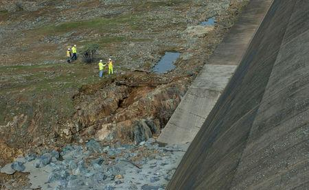 California Department of Water Resources crews inspect and evaluate the erosion just below the Lake Oroville Emergency Spillway site after lake levels receded, in Oroville, California, U.S., February 13, 2017.      Kelly M. Grow/ California Department of Water Resources/Handout via REUTERS