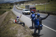 Venezuelan migrants hitchhike towards the capital, in Tunja, Colombia, Tuesday, Oct. 6, 2020. Amid COVID-19, drivers are more reluctant to pick up hitchhikers, shelters remain closed, and locals who fear contagion are less likely to help out with food donations. (AP Photo/Ivan Valencia)