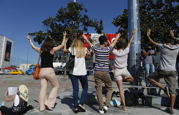 Young people practice yoga during a silent protest at Taksim Square in Istanbul, Turkey, Wednesday, June 19, 2013. After weeks of sometimes-violent confrontation with police, Turkish protesters have found a new form of resistance: standing still and silent. (AP Photo/Petr David Josek)