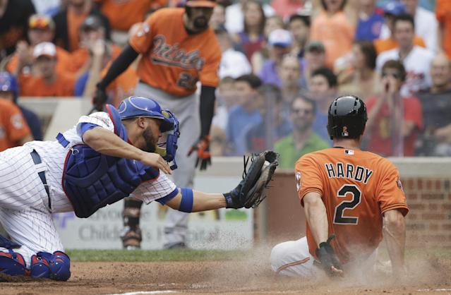Baltimore Orioles' J.J. Hardy (2) scores on a single by Bud Norris as Chicago Cubs catcher Welington Castillo is late with the tag during the second inning of an interleague baseball game in Chicago, Saturday, Aug. 23, 2014. (AP Photo/Nam Y. Huh)