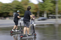 People ride on electric scooters in Paris, Monday, Aug. 12, 2019. The French government is meeting with people who've been injured by electric scooters as it readies restrictions on vehicles that are transforming the Paris cityscape. The Transport Ministry says Monday's closed-door meeting is part of consultations aimed at limiting scooter speeds and where users can ride and park them. (AP Photo/Lewis Joly)