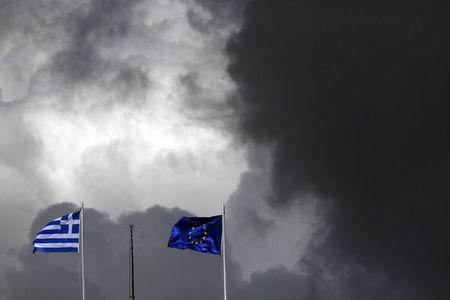 A European Union flag and a Greek national flag flutter atop a building in central Athens