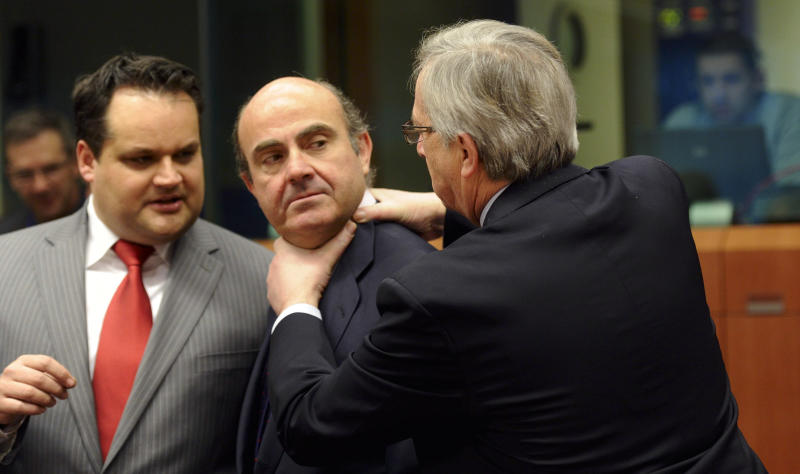 RETRANSMISSION TO ADD CONTEXT INFORMATION - Luxembourg's Prime Minister Jean-Claude Juncker, right, puts his hands on the neck of Spain's Economy Minister Luis de Guindos, center, as Dutch Finance Minister Jan Kees De Jager, left, looks on during a meeting of eurozone finance ministers at the EU Council building in Brussels on Monday, March 12, 2012. As ministers chatted with each other at the meeting, the eurogroup's chief, Jean-Claude Juncker, came up behind Spanish finance minister, Luis De Guindos, and jokingly grabbed him by the neck with both hands, but the gesture soon appeared to change into a laughing friendly greeting and then deep discussion. The 17 euro countries are trying to focus on issues beyond the Greek crisis and deal with longer-term issues in their currency union, like discussing Spain's high deficits and potentially dangerous imbalances in some countries. (AP Photo/Virginia Mayo)