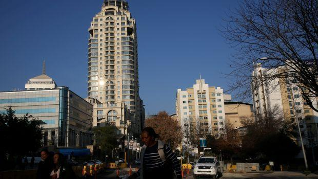 Michelangelo towers are seen as pedestrians make their way to work past road construction site in Sandton, South Africa.