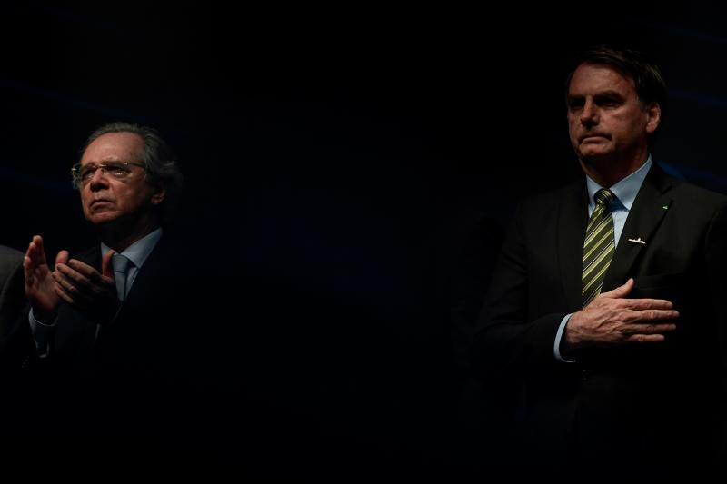 Brazil's Economy Minister Paulo Guedes (L) applauds next to Brazilian President Jair Bolsonaro during the ceremony marking the assembly of the parts of Brazil's new Navy submarine Humaita (SBR-2), at the Itaguai Navy Complex in Rio de Janeiro, Brazil, on October 11, 2019. (Photo by MAURO PIMENTEL / AFP) (Photo by MAURO PIMENTEL/AFP via Getty Images)