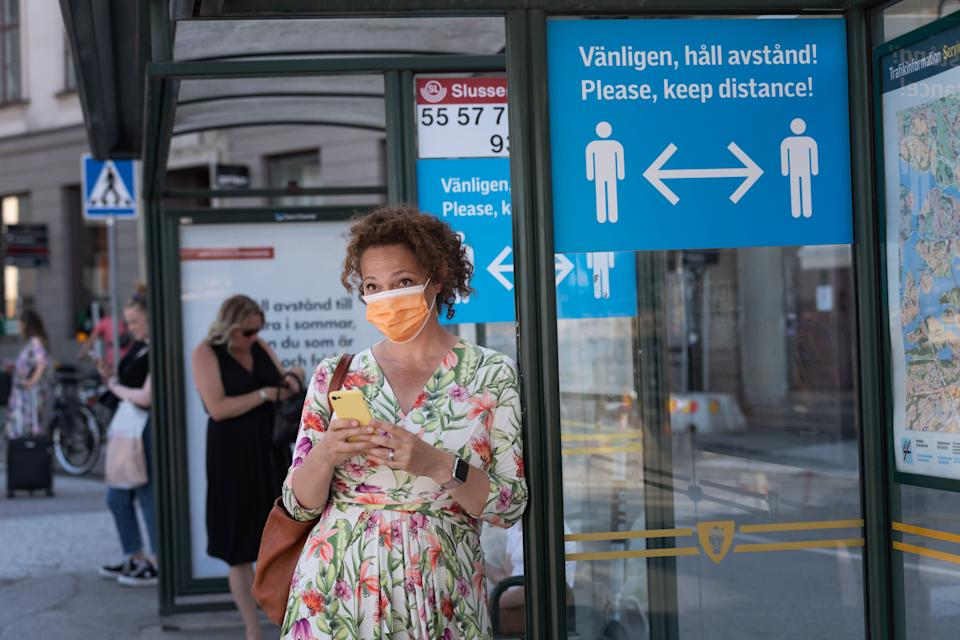 A woman wears a face mask as she waits at a bus stop with an information sign asking people to keep social distance due to the coronavirus COVID-19 pandemic on June 26, 2020 in Stockholm, Sweden. (Photo by Stina STJERNKVIST / various sources / AFP) / Sweden OUT (Photo by STINA STJERNKVIST/TT News Agency/AFP via Getty Images)