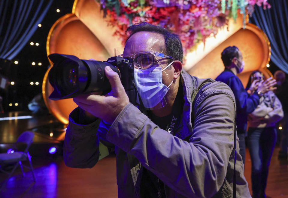 In this image courtesy of Robert Gauthier, AP staff photographer Chris Pizzello photographs the 63rd annual Grammy Awards on Thursday, March 11, 2021 in Los Angeles. (Robert Gauthier via AP)
