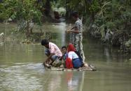 Villager uses a raft to move across a flooded locality in a flood effected village in Morigaon district of Assam in India on Friday, 17 July 2020. (Photo by David Talukdar/NurPhoto via Getty Images)