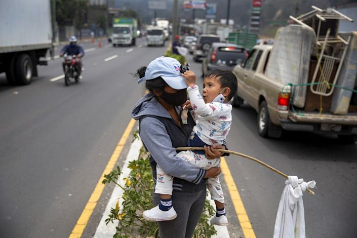 "A woman with her son holds a white flag as a sign that she needs food assistance Wednesday in Villa Nueva, Guatemala. <span class=""copyright"">(Moises Castillo / Associated Press)</span>"