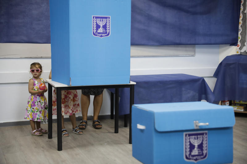 A woman votes at a polling station in Rosh Haayin, Israel, Tuesday, Sept. 17, 2019. Israelis began voting Tuesday in an unprecedented repeat election that will decide whether longtime Prime Minister Benjamin Netanyahu stays in power despite a looming indictment on corruption charges. (AP Photo/Sebastian Scheiner)