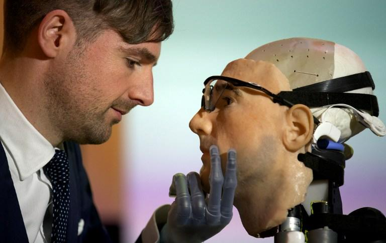 "Researcher Bertolt Meyer, a lifelong user of prosthetic technology and the model for ""Rex"", the world's first ""bionic man"", poses with the humanoid during a photo call at the Science Museum in London on February 5, 2013. The 640,000 GBP (1 million US dollars) bionic has a distinctly human shape and boasts prosthetic limbs, a functional artificial blood circulatory system complete with artificial blood, as well as an artificial pancreas, kidney, spleen and trachea. Rex will be displayed at the Science Museum from February 7.  AFP PHOTO/ANDREW COWIE"