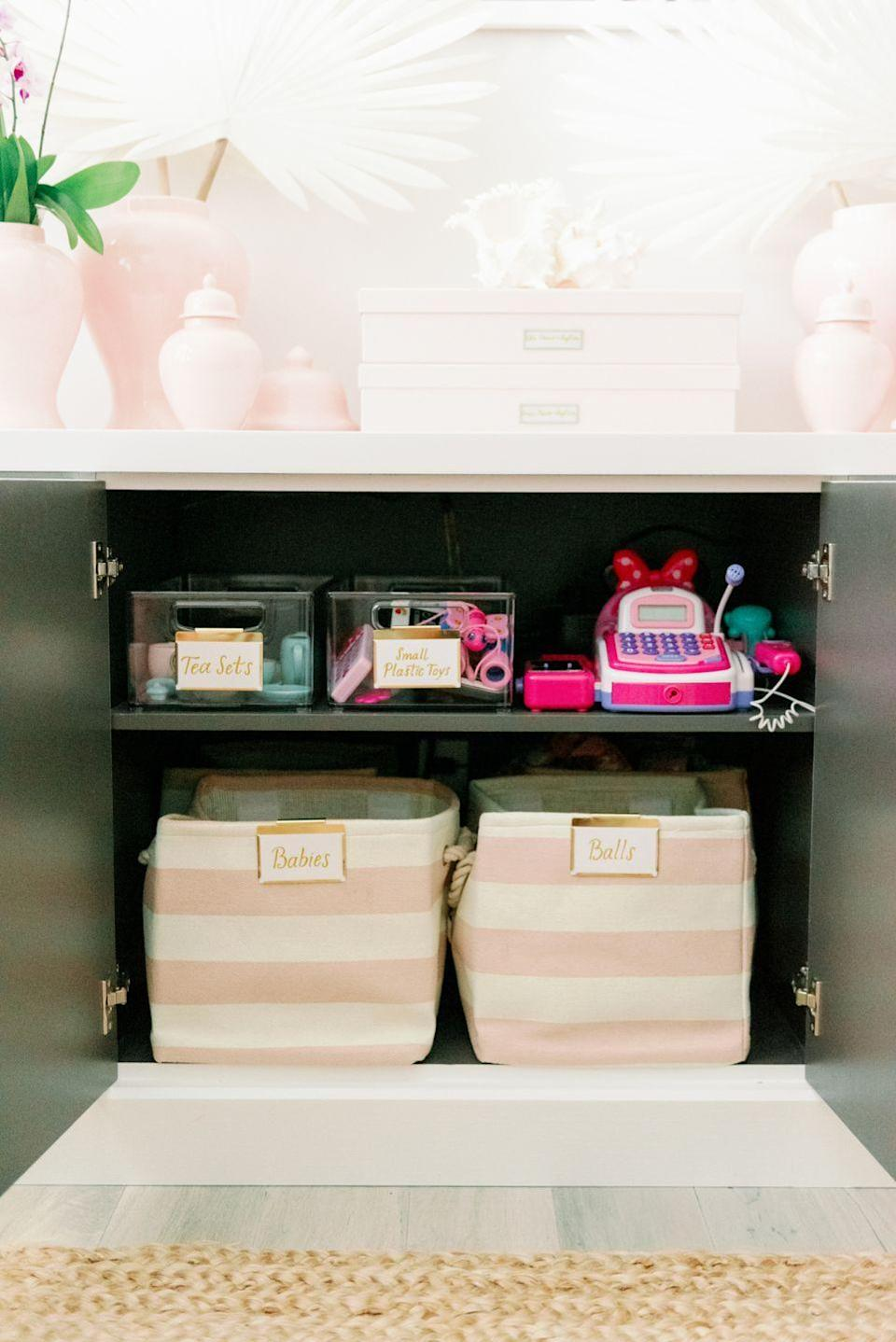 """<p>Don't just stuff everything in the closet! By keeping bins tucked away in cabinets, clutter will be kept at bay even behind the scenes.</p><p><strong>See more about this project from <a href=""""https://www.palmbeachlately.com/2019/09/15/home-organizing-beths-office-playroom-with-urban-simplicity-and-the-container-store/"""" rel=""""nofollow noopener"""" target=""""_blank"""" data-ylk=""""slk:Palm Beach Lately, Urban Simplicity, and The Container Store"""" class=""""link rapid-noclick-resp"""">Palm Beach Lately, Urban Simplicity, and The Container Store</a>.</strong></p><p><strong><strong><a class=""""link rapid-noclick-resp"""" href=""""https://www.amazon.com/TheWarmHome-Foldable-Storage-Collapsible-15-711-88-3/dp/B07BF73TT1?tag=syn-yahoo-20&ascsubtag=%5Bartid%7C10063.g.36014277%5Bsrc%7Cyahoo-us"""" rel=""""nofollow noopener"""" target=""""_blank"""" data-ylk=""""slk:SHOP FABRIC BASKETS"""">SHOP FABRIC BASKETS</a></strong><br></strong></p>"""