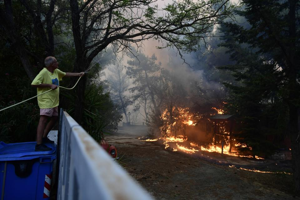 A man drops water to burning trees during a wildfire in Adames area, northern Athens, Greece, Tuesday, Aug. 3, 2021. Hundreds of residents living near a forest area north of Athens fled their homes Tuesday as a wildfire reached residential areas as Greece grappled with its worst heatwave in decades. (AP Photo/Michael Varaklas)