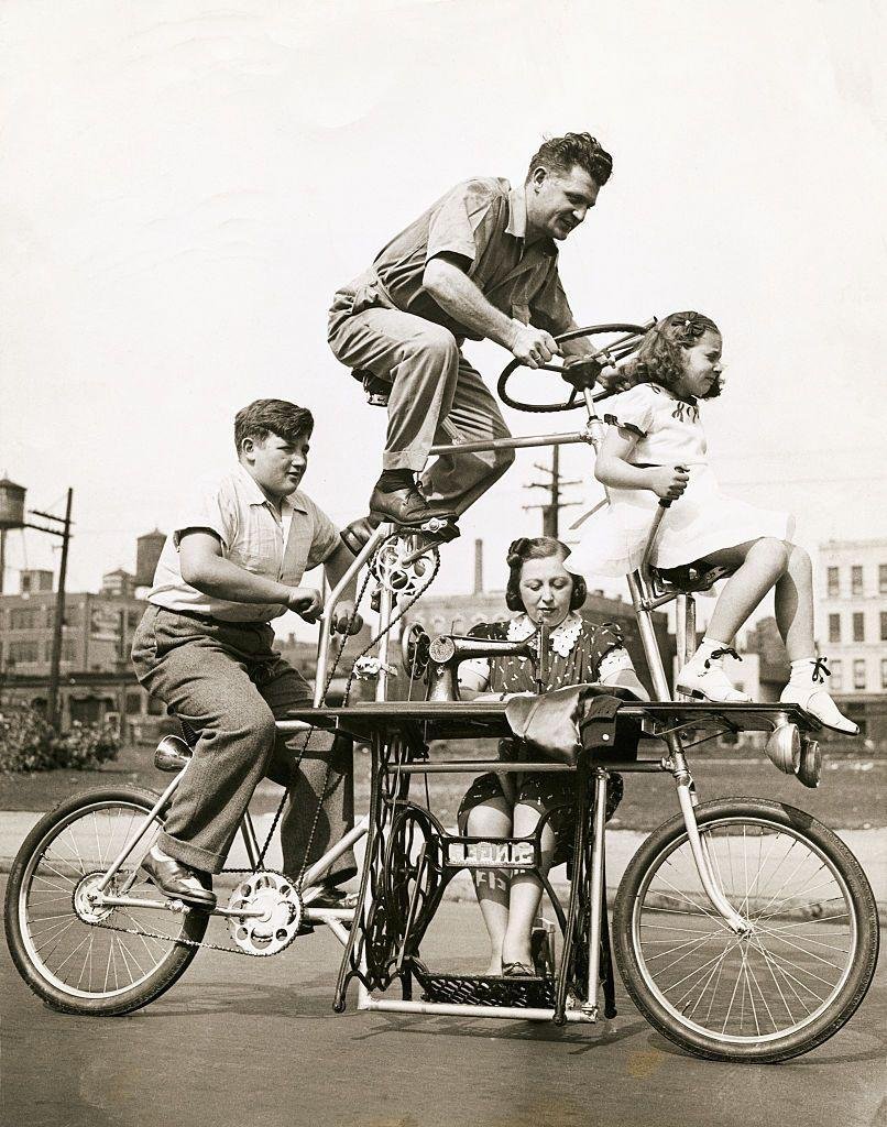 <p>A family bikes down the street in a 1939 four-person bicycle invention, which includes two levels and a sewing machine station. </p>