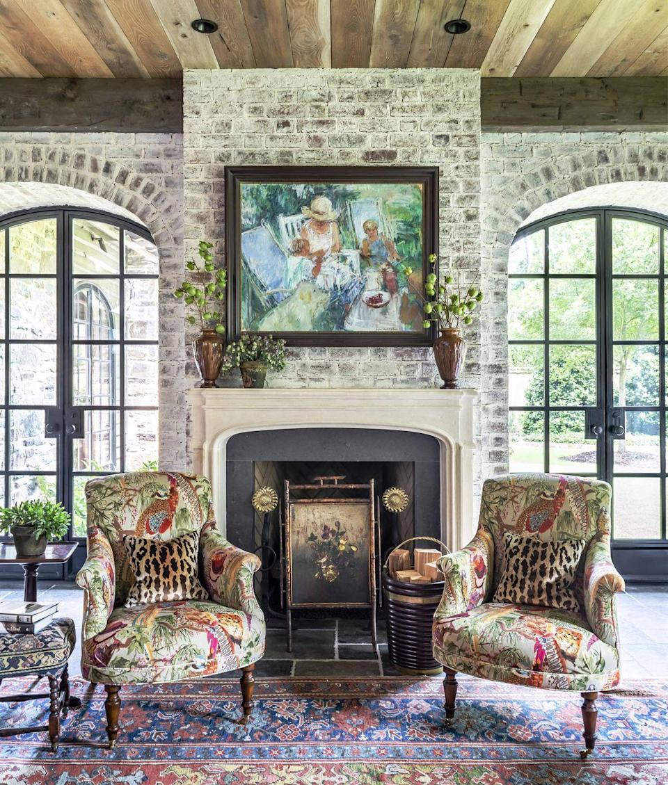 <p>Direct repetition of color helps to make pattern-mixing feel effortless. Here, an antique French painting with blues, reds, and greens picks up a similar palette in the chairs and carpet. The limestone mantel echoes the limewashing of the brick. </p>
