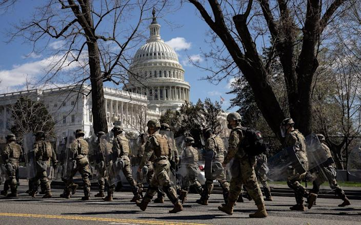 Members of US Capitol police and national guard walk near the scene after a police officer died Friday - Getty