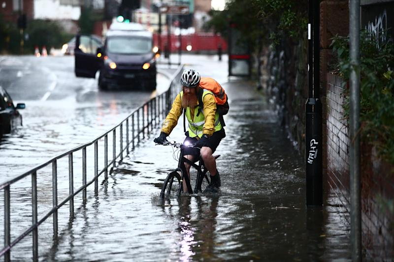 A man cycles through a flooded street Sheffield, after torrential rain in the area - but more is expected overnight (PA)