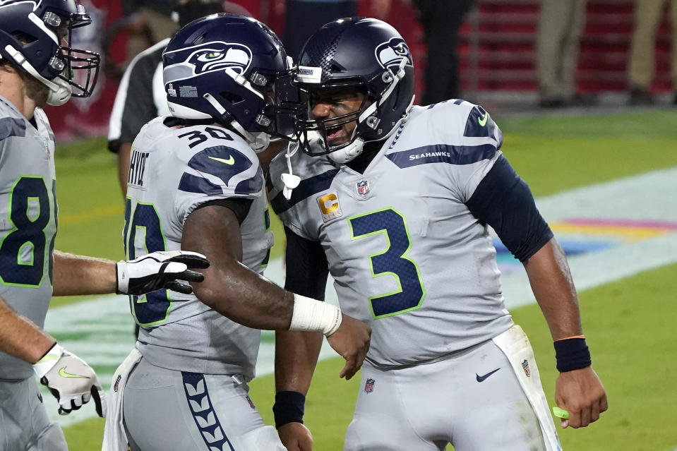 Seattle Seahawks running back Carlos Hyde (30) celebrates his touchdown with quarterback Russell Wilson (3) during the first half of an NFL football game against the Arizona Cardinals, Sunday, Oct. 25, 2020, in Glendale, Ariz. (AP Photo/Rick Scuteri)