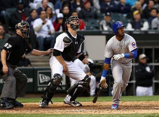Chicago Cubs' Julio Borbon along with umpire Scott Barry and Chicago White Sox catcher Tyler Flowers watch Borbon's ball go over the right field wall for a two run home run in the fifth inning giving the Cubs a 3-0 lead in a baseball game in Chicago on Monday, May 27, 2013. (AP Photo/Charles Cherney)