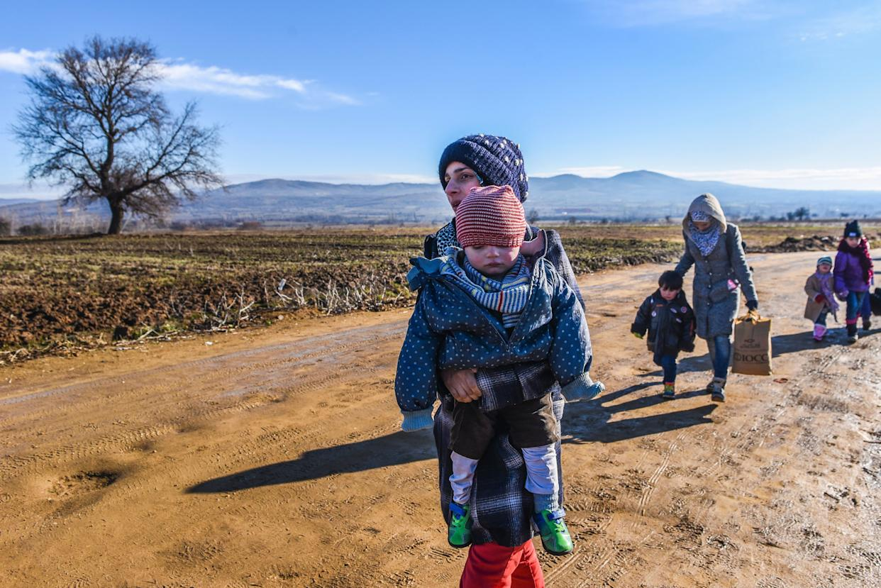 Migrants and refugees walk on January 8, 2016 after crossing the Macedonian border in the Serbian village of Miratovac.