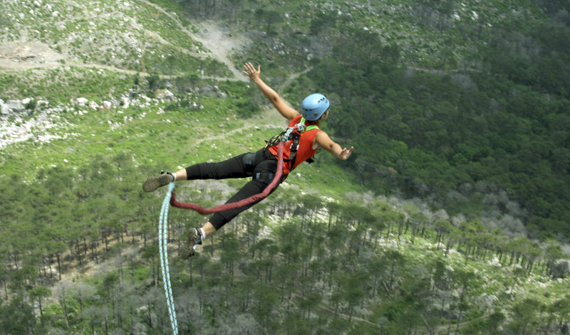 A woman jumps from a cliff into the abyss.