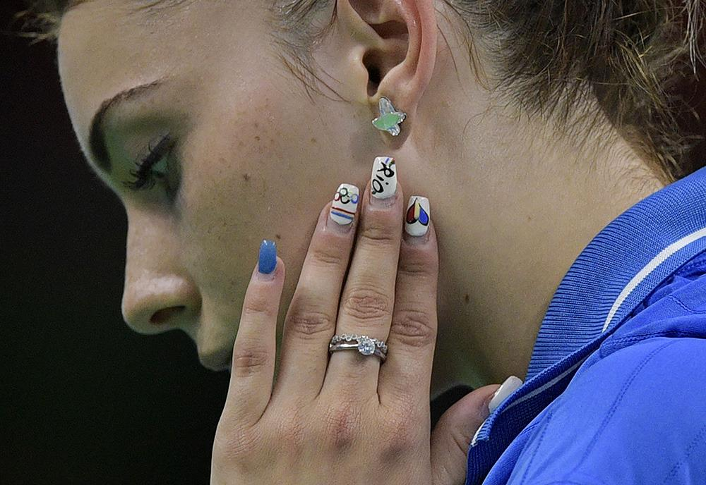<p>Romania's Bernadette Szocs displays Olympics-themed nail art during a women's team qualification round table tennis match against South Korea. (Photo: Getty Images)</p>