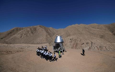 A group of students walk past a model of a lander - Credit: Wang Zhao AFP
