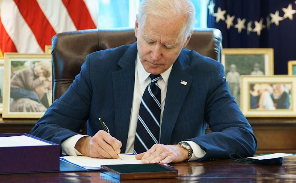 US President Joe Biden signs the American Rescue Plan on March 11, 2021, in the Oval Office of the White House in Washington, DC. - Biden signed the $1.9 trillion economic stimulus bill and will give a national address urging