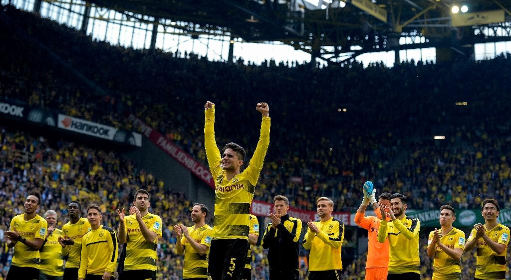 Dortmund's defender Marc Bartra (C) celebrates with his teammates after a German first division football match against Werder Bremen in Dortmund, western Germany, on May 20, 2017 (AFP Photo/SASCHA SCHUERMANN)